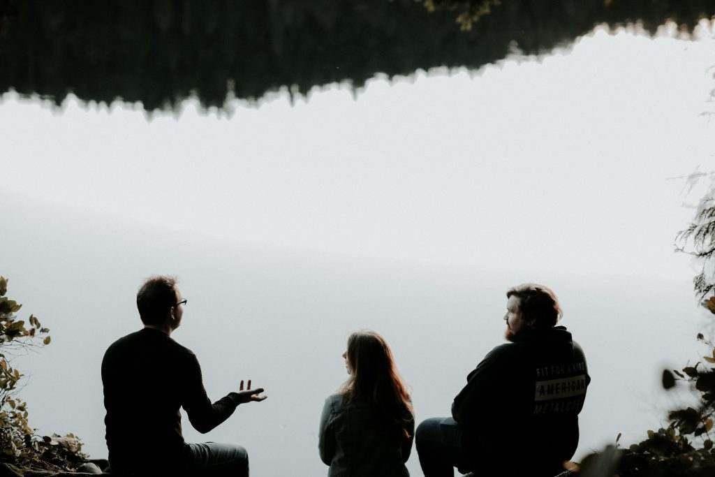 Three people sitting and talking by a body of water.